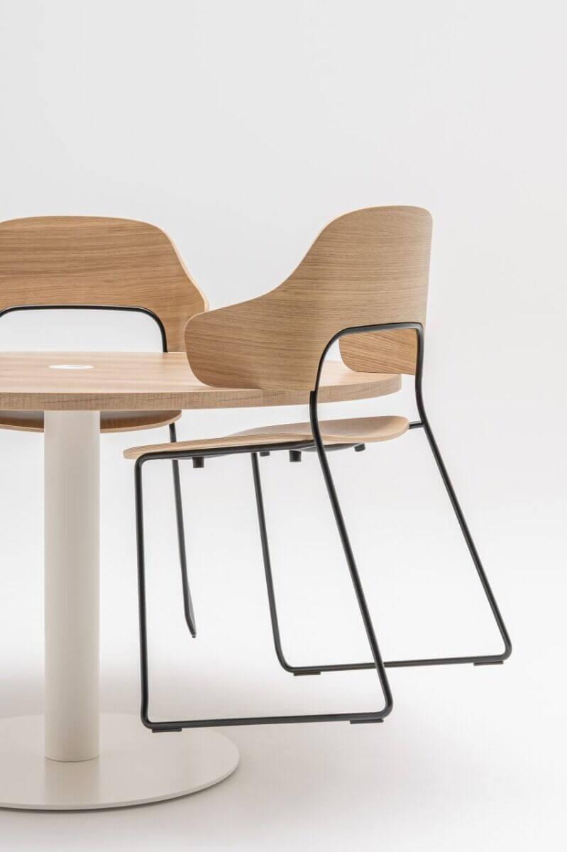 La chaise de restaurant design FEEL possède des accoudoirs qui permettent de la suspendre à la table.